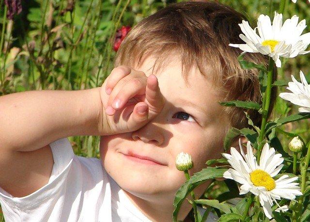 Мальчик смотрит на солнце и закрывает рукой один глаз