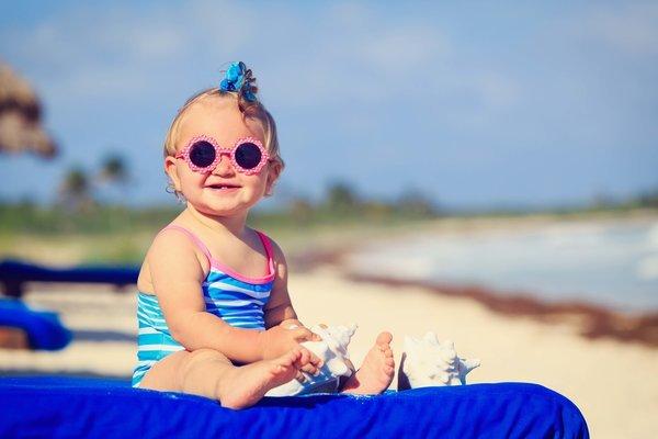 Годовалая девочка на пляже в солнечных очках