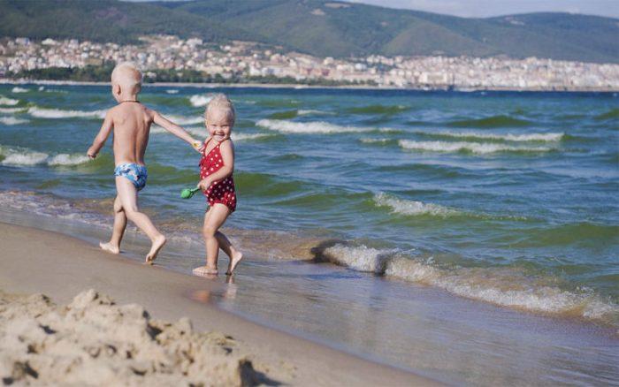 Мальчик и девочка бегут по побережью