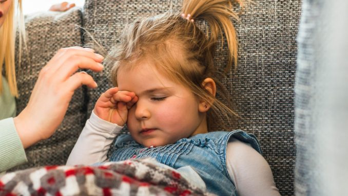 Девочка закрыла глаза и лежит на диване под одеялом
