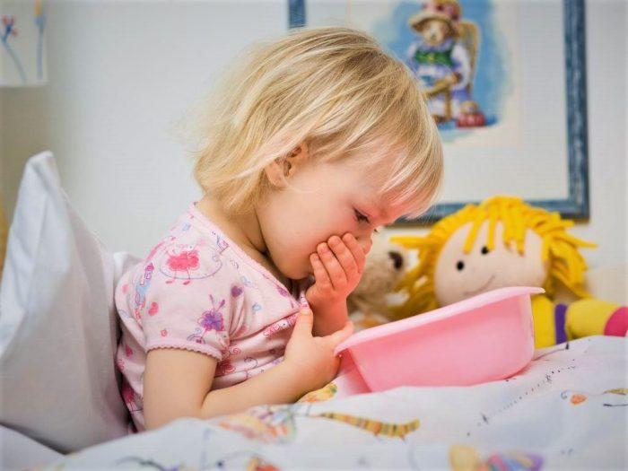 Девочка склонилась над тазиком и прикрывает рот рукой