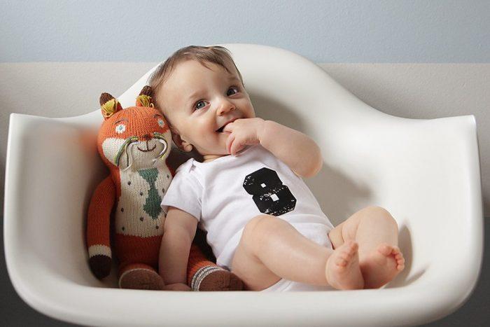 Младенец сидит и держит пальцы во рту, на кофточке у него цифра 8