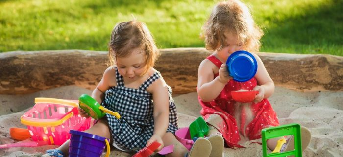 Девочки играют в песочнице