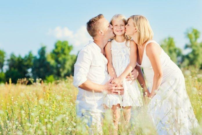 Родители обнимают и целуют дочку, та счастливо улыбается