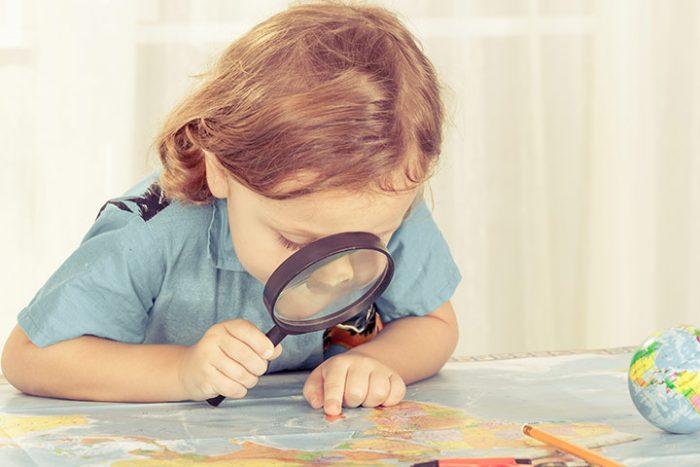 Девочка через лупу рассматривает карту мира