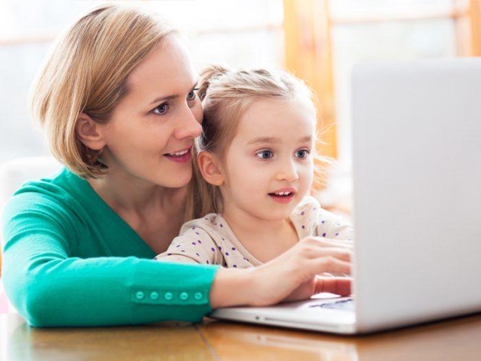 Мама с дочкой смотрят в экран ноутбука
