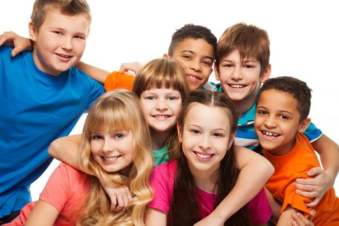 Компания детей-сверстников (все улыбаются и обнимают друг друга)