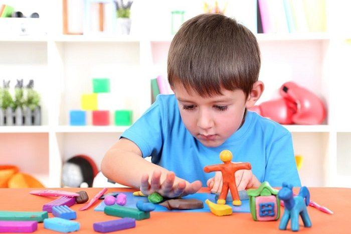 Мальчик сосредоточенно лепит из пластилина