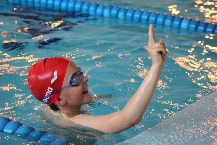 Мальчик доплыл до конца дорожки в бассейне (радостно показывает пальцем цифру 1)