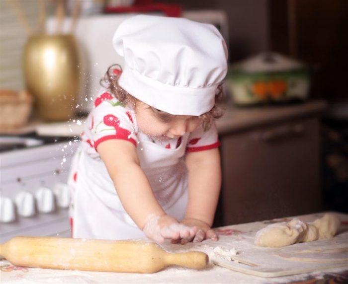 Маленькая девочка на кухне раскатывает тесте, от её ручек летит мука