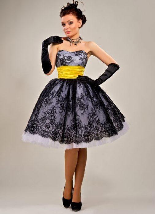 Девушка в коротком выпускном платье с широким поясом