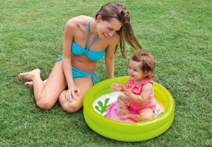 ребёнок в маленьком надувном бассейне и мама