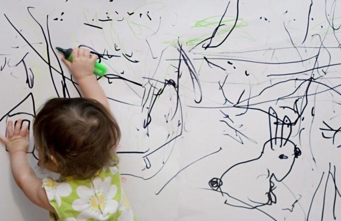 Маленький ребёнок рисует чёрным фломастером