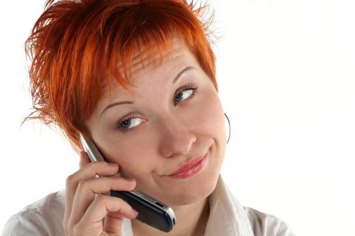 Женщина разговаривает по телефону с отстранённым видом