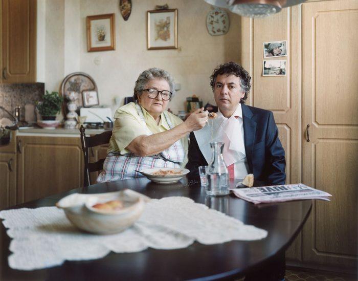 Старая мать кормит пожилого сына с ложечки