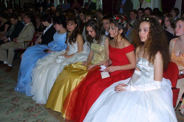 Девушки в пышных вечерних платьях сидят в актовом зале