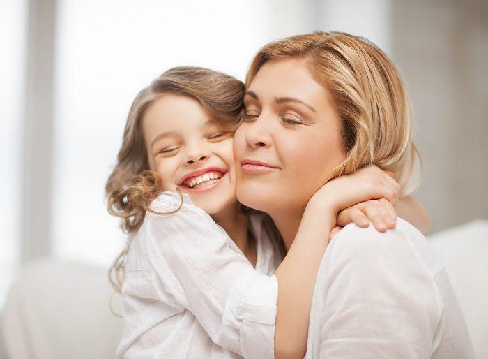 Мама обнимается с дочкой, обе счастливо улыбаются