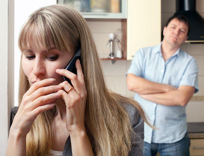 Жена разговаривает по телефону, муж скрестил руки и смотрит на неё с недовольным видом
