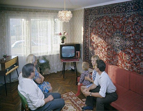 Семья смотрит телевизор (молодые с ребёнком и родители)