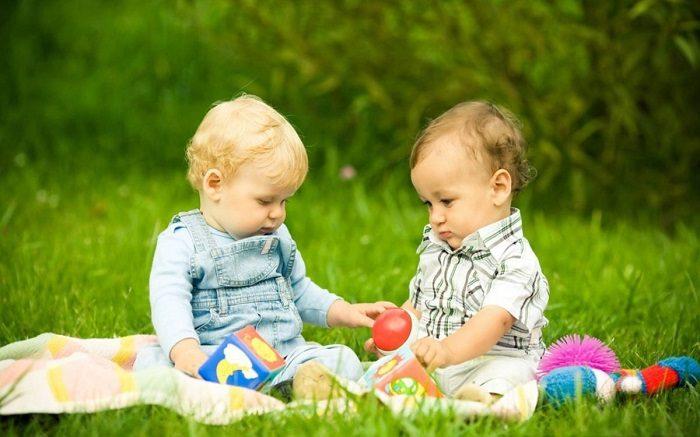Маленькие дети сидят с игрушками на одеяле на природе