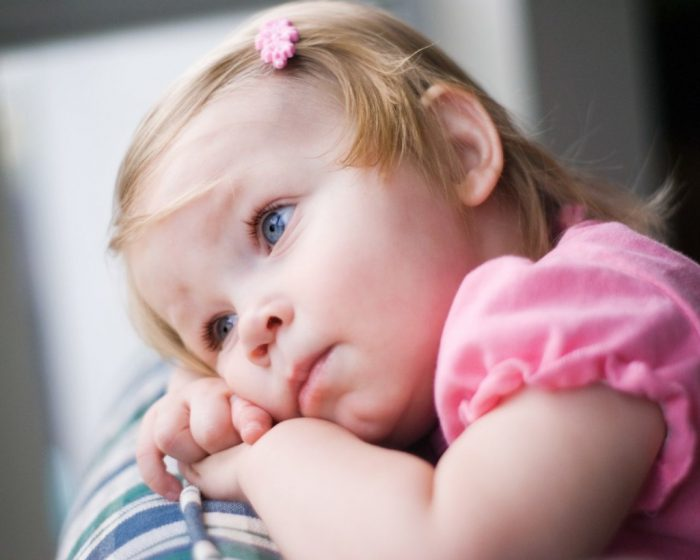 Маленькая грустная девочка на руках у взрослого