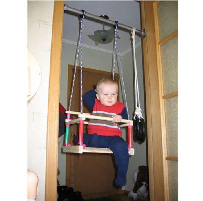 Мальчик в детских домашних качелях