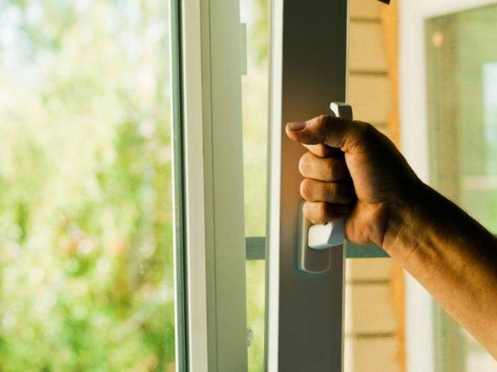 Мужчина открывает окно