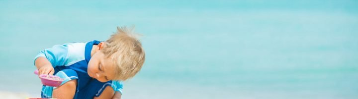 мальчик играет с песком на пляже