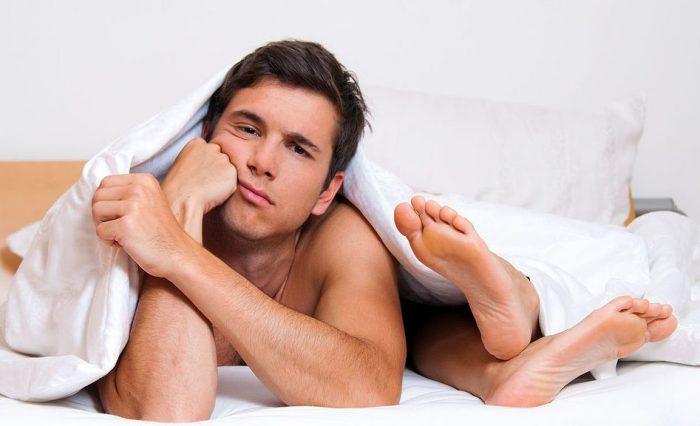 Грустный мужчина в постели