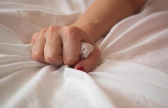 Рука сжимает простынь