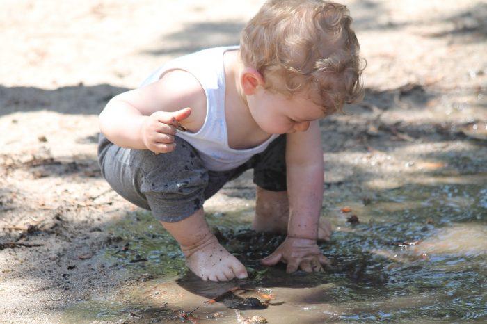 мальчик сует руку в лужу