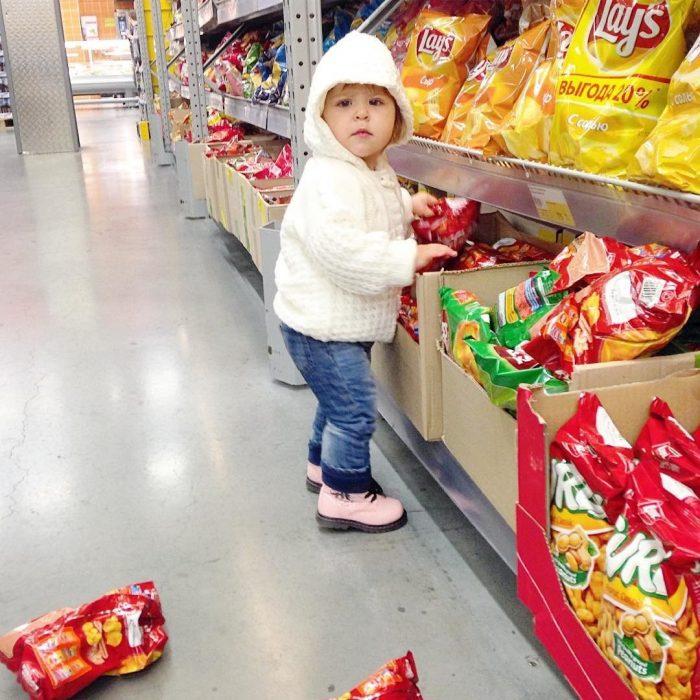 девочка достает чипсы с полки