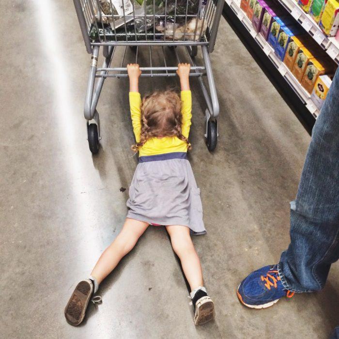 девочка висит на магазинной тележке