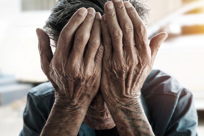 Пожилой мужчина закрывает лицо руками