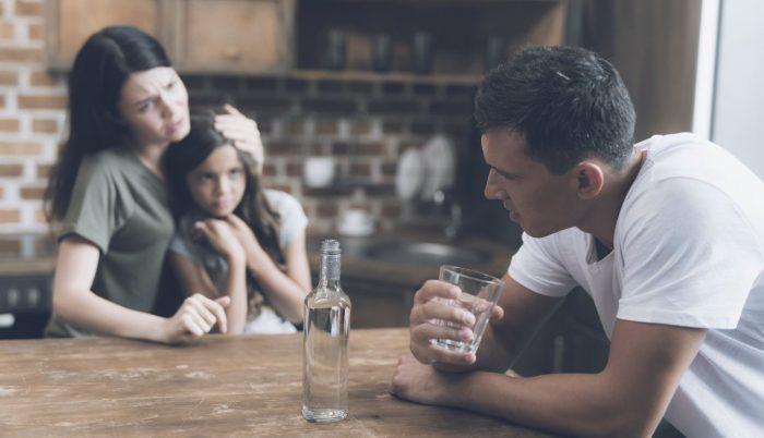 Мужчина с бутылкой водки и его семья