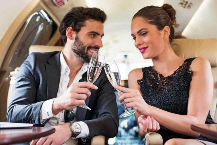 мужчина и женщина пьют шампанское в самолете