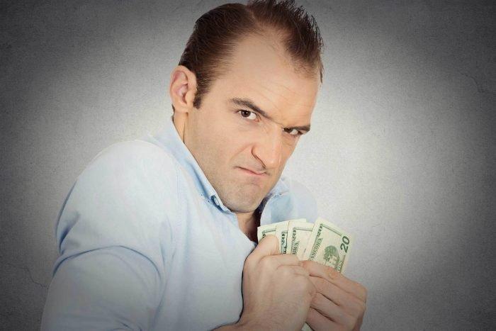 Мужчина прижимает к себе деньги