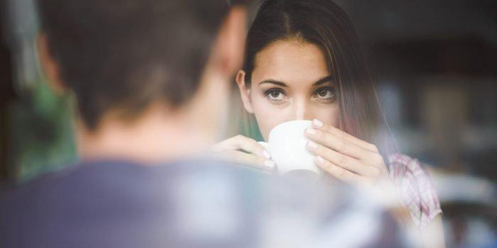 женщина пьет чай и смотрит на мужчину напротив