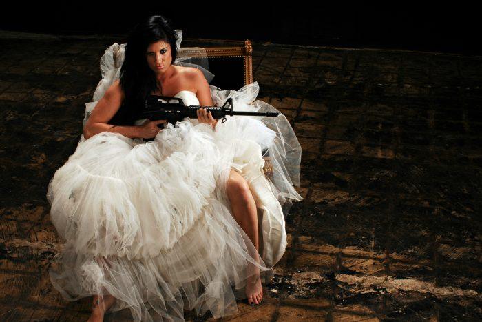 Девушка в свадебном платье с автоматом сидит на стуле