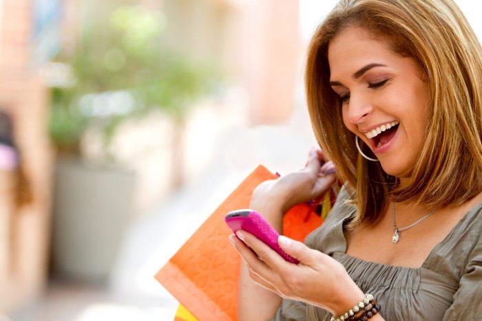 Девушка улыбается, глядя в телефон