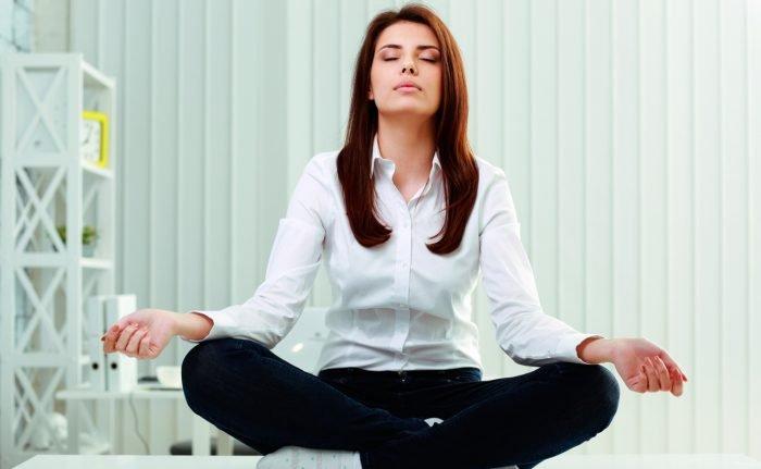 Девушка медитирует в офисе