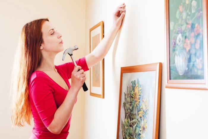 Девушка забивает гвоздь в стену
