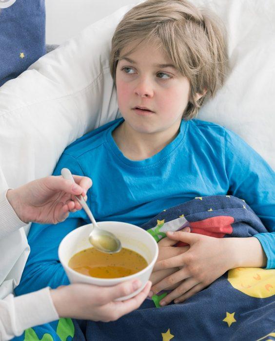Больного ребенка кормят куриным бульоном