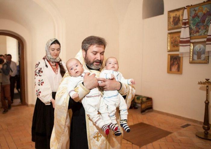 Батюшка несёт на руках двойняшек — мальчика и девочку