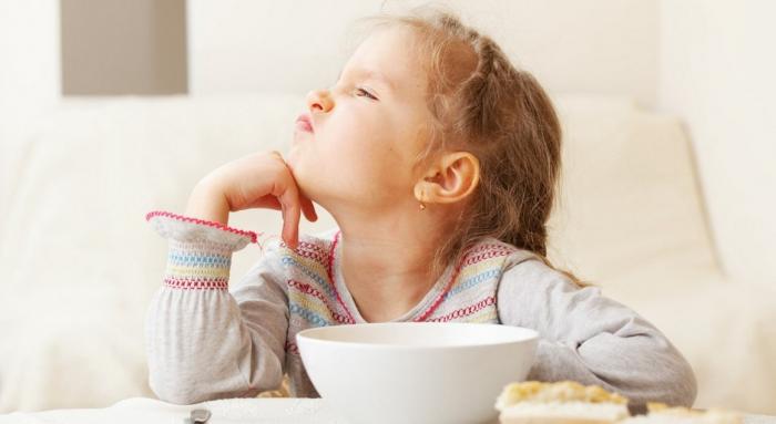 Девочка отвернулась от тарелки с супом