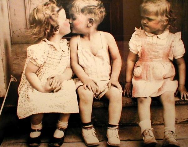 Мальчик целует девочку, другая девочка завистливо на них смотрит