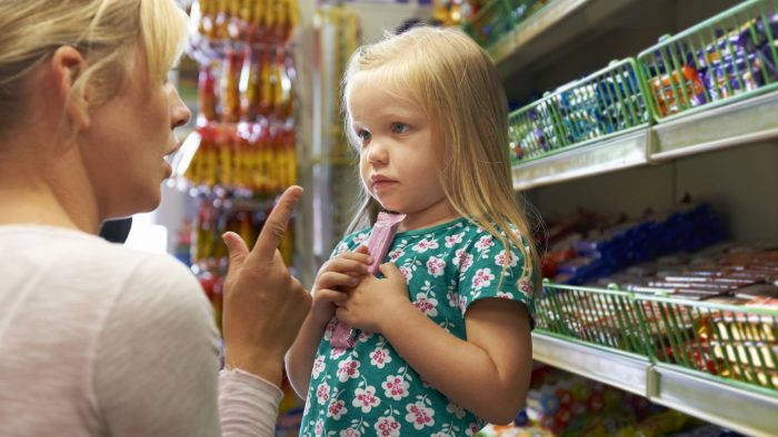В магазине девочка прижимает к груди конфету, мама что-то ей объясняет