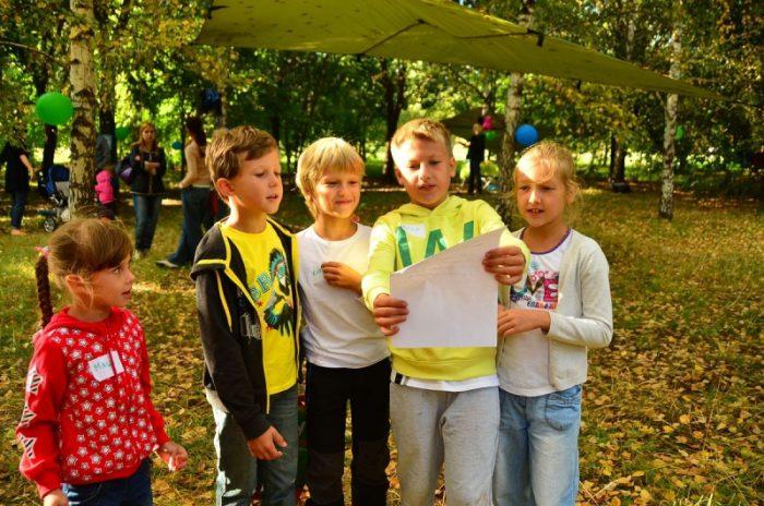 Дети в парке читают текст на листе бумаги