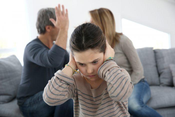 Девочка заткнула уши, чтобы не слышать ссору родителей