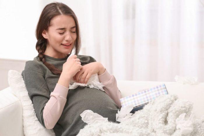 Беременная сидит на диване и плачет, рядом куча использованных салфеток